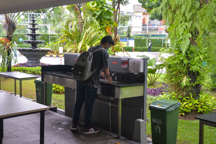 A JIS student washes his hands at the available facilities in the school. Wednesday marks the limited reopening trial of schools using the blended learning system..