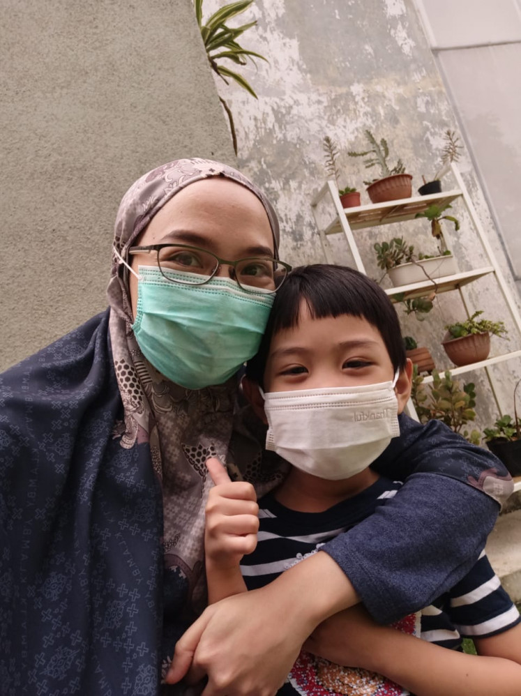 Raya poses with his working mother, Mirza, whom he depends on to help with his schoolwork during online learning.