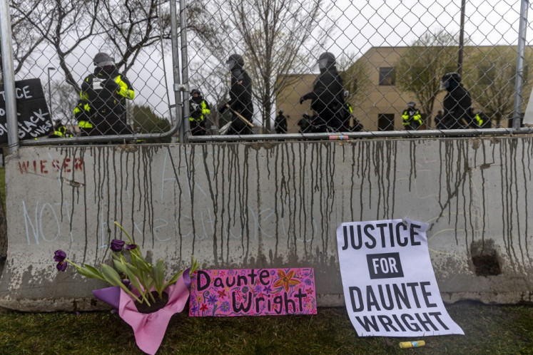 Flowers and signs are left in front of the security fence at the start of curfew to protest the death of Daunte Wright who was shot and killed by a police officer in Brooklyn Center, Minnesota on April 12, 2021. A suburb of Minneapolis was under curfew early April 12, 2021 after US police fatally shot a young Black man, sparking protests not far from where a former police officer was on trial for the murder of George Floyd.Hundreds of people gathered outside the police station in Brooklyn Center, northwest of Minneapolis, with police later firing teargas and flash bangs to disperse the crowd, according to an AFP videojournalist.