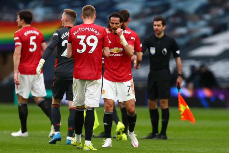 Manchester United's Scottish midfielder Scott McTominay celebrates with Manchester United's Uruguayan striker Edinson Cavani following their 3-1 win in the English Premier League football match between Tottenham Hotspur and Manchester United at Tottenham Hotspur Stadium in London, on April 11, 2021.