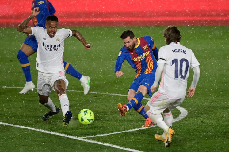 Real Madrid's Brazilian defender Eder Militao (L) and Real Madrid's Croatian midfielder Luka Modric challenge Barcelona's Argentinian forward Lionel Messi (C) during the