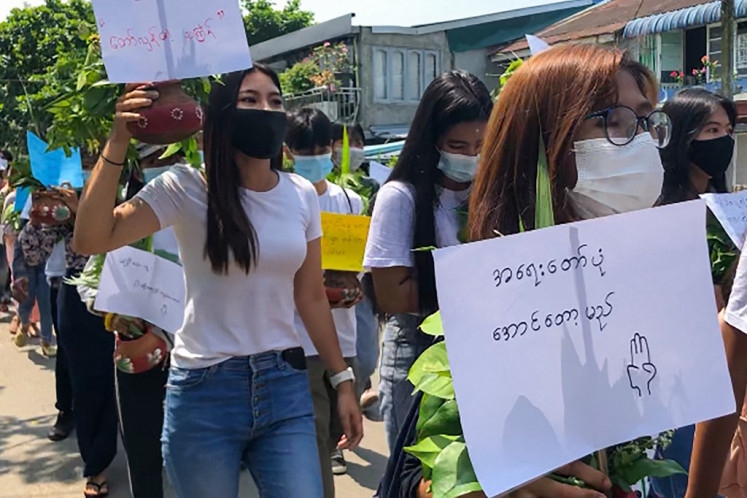 Protesters carry pots filled with Thingyan festival flowers and leaves as they hold signs during a demonstration against the military coup in Yangon on April 13, 2021.