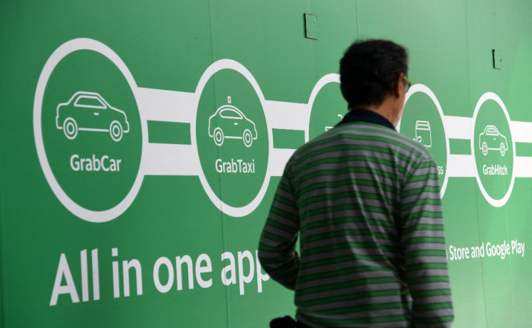 A man walk past the Grab transport office in Singapore on June 13, 2018. Toyota said on June 13, it was investing 1 billion US dollars in Asia ride-share company Grab, as the Japanese automaker looks to expand beyond its core business into the