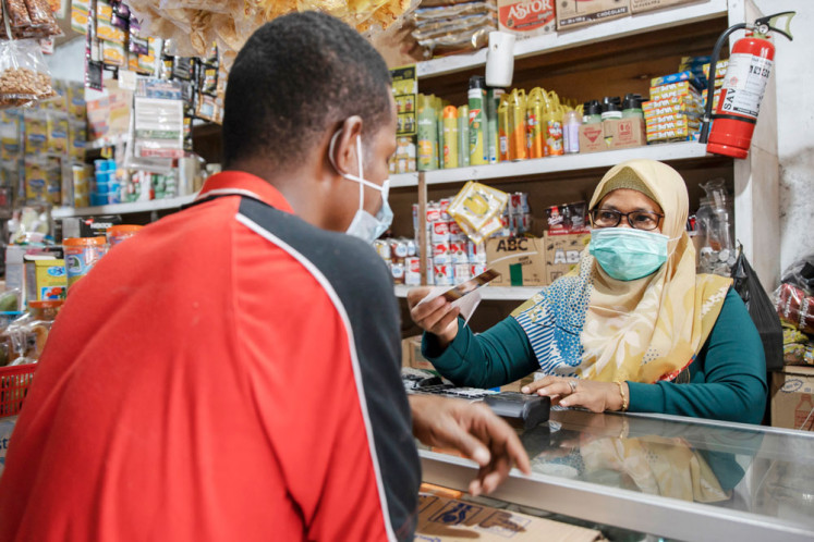 Sugiyati, a GrabKios agent partner in Jayapura, now helps hundreds of unbanked sellers in Abepura Market carry out transactions.