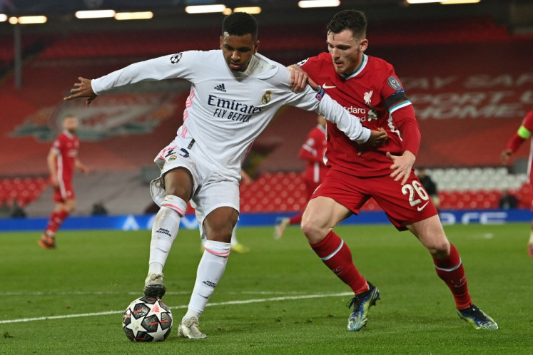 Real Madrid's Brazilian forward Rodrygo (L) vies with Liverpool's Scottish defender Andrew Robertson during the UEFA Champions League quarter final second leg football match between Liverpool and Real Madrid at Anfield in Liverpool, north west on April 14, 2021.
