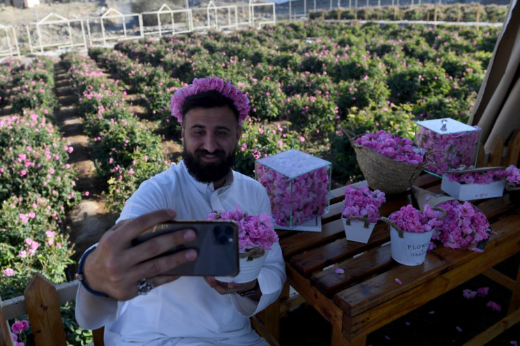 A tourist takes a photo with Taif roses at the Bin Salman Farm in the Saudi city of Taif on March 13, 2021. The family farm is open to visitors and offers a complete rural experience including the viewing of the time-honoured tradition of extracting rose water and oil from the Taif rose, a prized component in the cosmetic, culinary and other industries. It has become synonymous with the city itself, dubbed locally as the City of Roses.