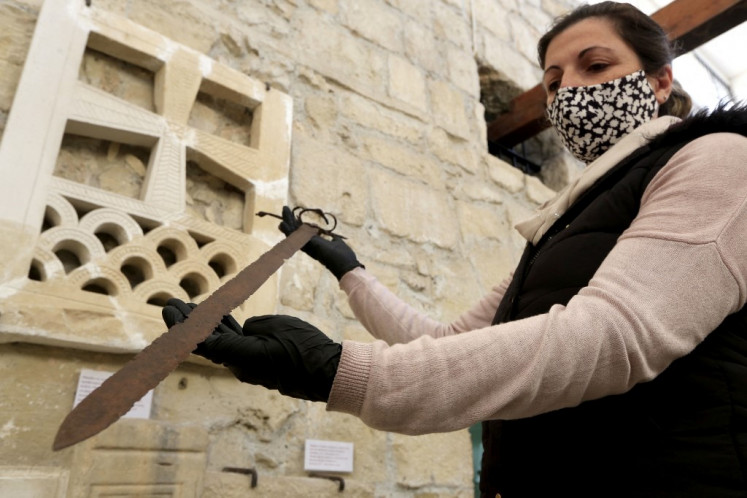 Archaeological officer Elena Stylianou shows a sword thought to be from the period of the crusades, on January 22, 2021, on the site where a chapel of the Knights Templar was built at the Limassol medieval castle, now housing the Cyprus Medieval Museum in the coastal Cypriot city. Fables of the Knights Templar are legend, but deep beneath a castle on Cyprus -- an island once owned by the Crusader brotherhood -- lies a legacy historians say still resonates today.