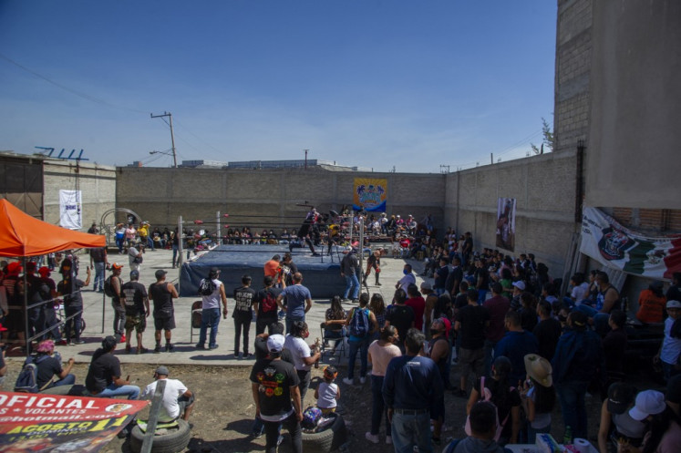 Fans cheer as Mexican wrestlers take part in a clandestine backyard show Hall of Fame, mounted by extreme wrestling organizer Zona 23, which pays tribute to wrestler Israel Montiel Leon,