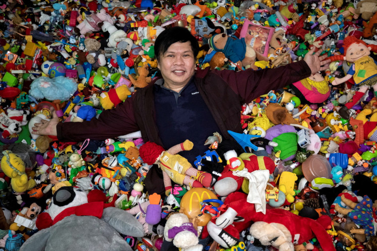 Drowning in toys: Percival Lugue, who has the Guinness world record for the largest fast-food toy collection, poses with his toy collection in his home in Apalit, Pampanga province, Philippines, April 20, 2021.