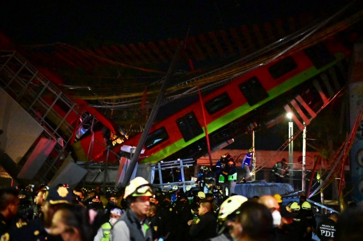 Rescue workers gather at the site of a metro train accident after an overpass for a metro partially collapsed in Mexico City on May 3, 2021. At least 13 people were killed and dozens injured in a metro train accident in the Mexican capital on May 3, the authorities said.