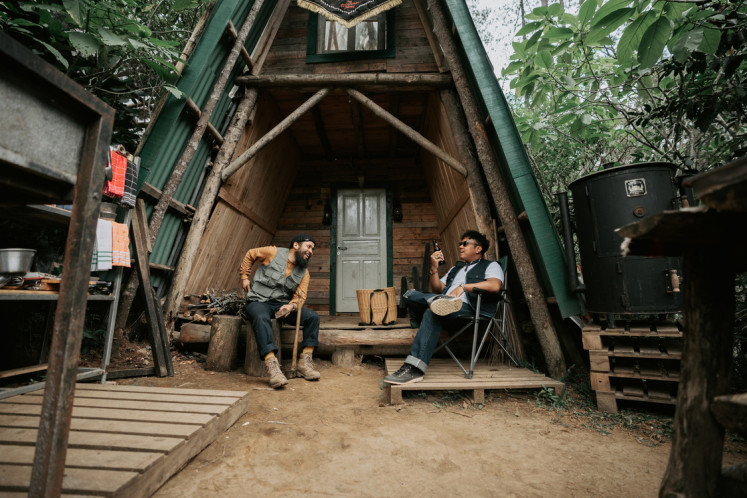 Back to nature: Gianjar and Hedi relax in front of Saux Farm's wooden cabin.