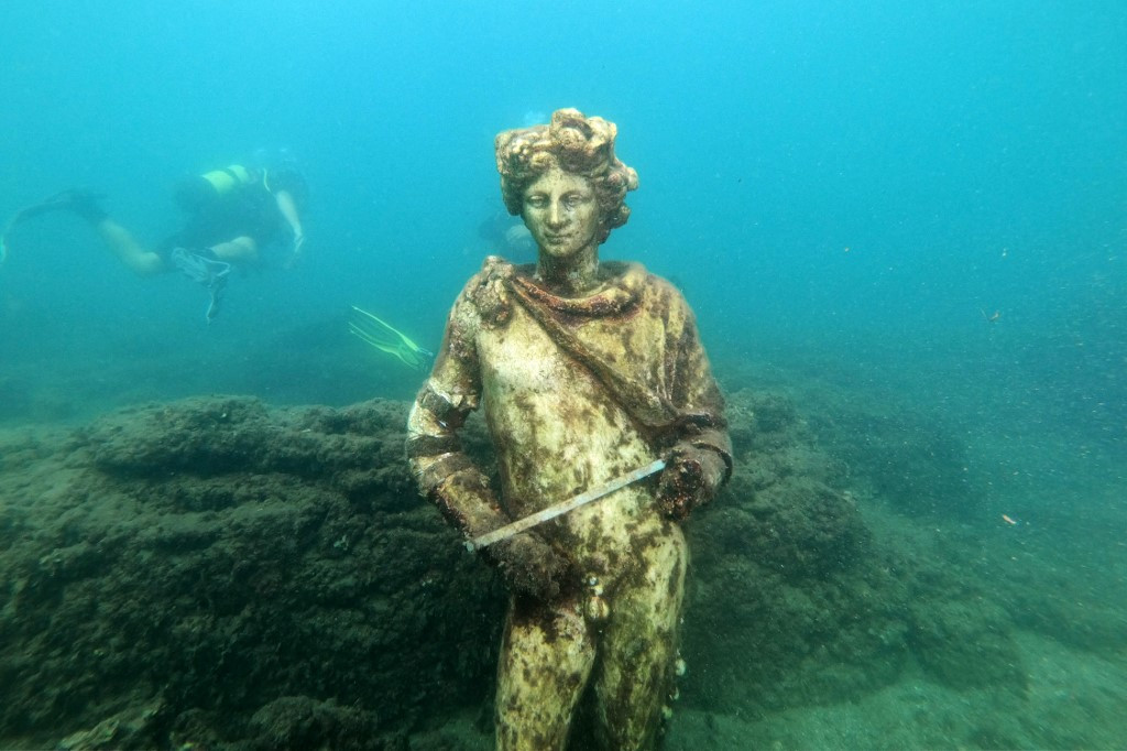 0 SHARES In this photograph taken on August 18, 2021 a dive guide shows tourists a copy of the original statue preserved at the Museum of Baiae, representing Dionysus with ivy crown in the Nymphaeum of punta Epitaffio, the submerged ancient Roman city of Baiae at the Baiae Underwater Park